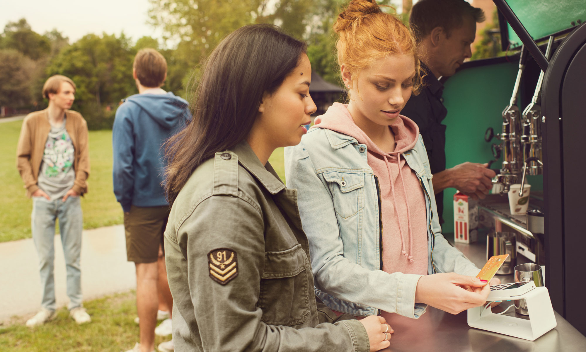 Two young women buying coffee from foodtruck.